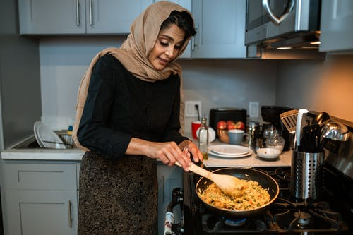 Woman in Black Long Sleeve Shirt and Gray Hijab Holding Brown Wooden Ladle