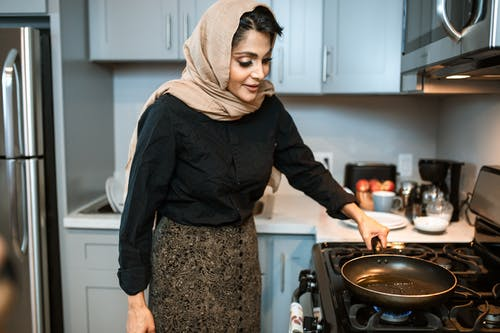 Content Arabic woman standing with frying pan in kitchen