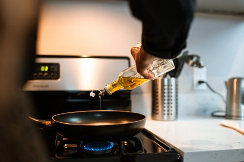 Crop faceless chef pouring oil in pan