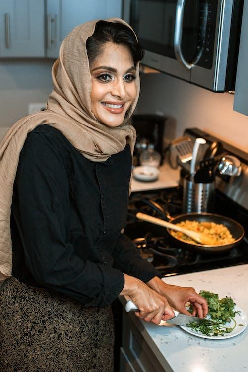 Mujer En Camisa De Manga Larga Negra E Hijab Marrón Sentada En Una Silla