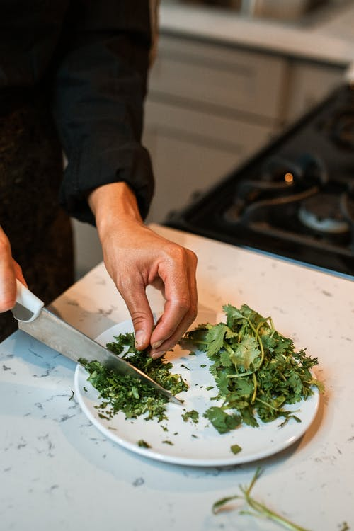 Person Holding Knife Slicing Green Vegetable