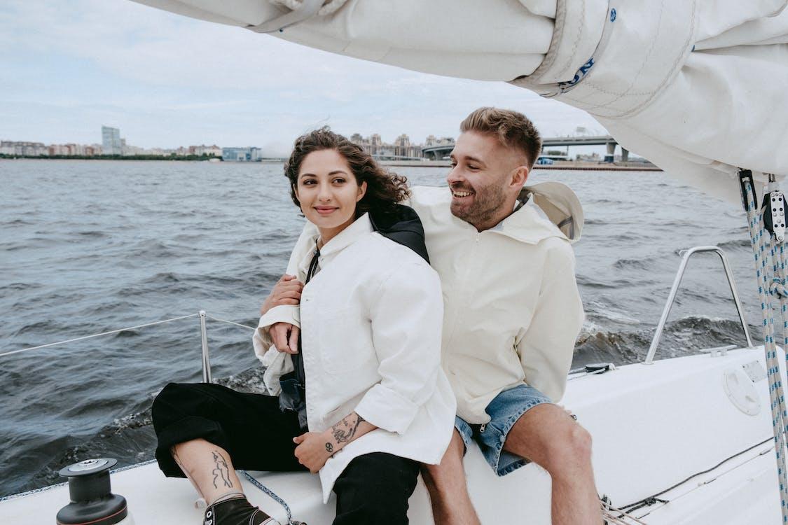 Man in White Suit Jacket Sitting Beside Woman in Blue Denim Shorts on Boat