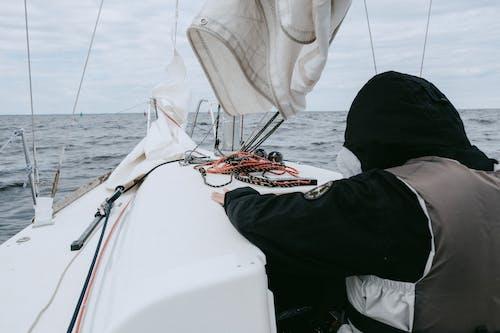 Siyah Pantolonlu Beyaz Teknede Oturan Kişi