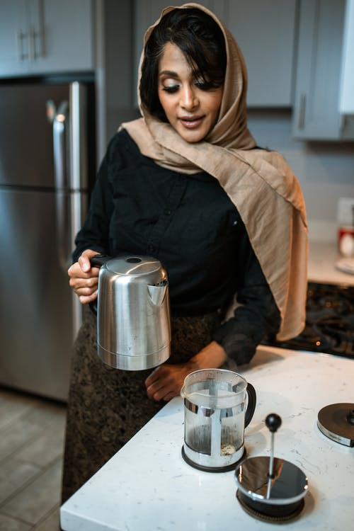 A Woman Holding a Silver Kettle