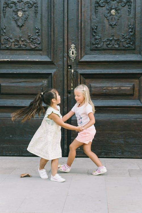 Kahverengi Ahşap Kapının Yanında Duran 2 Kız