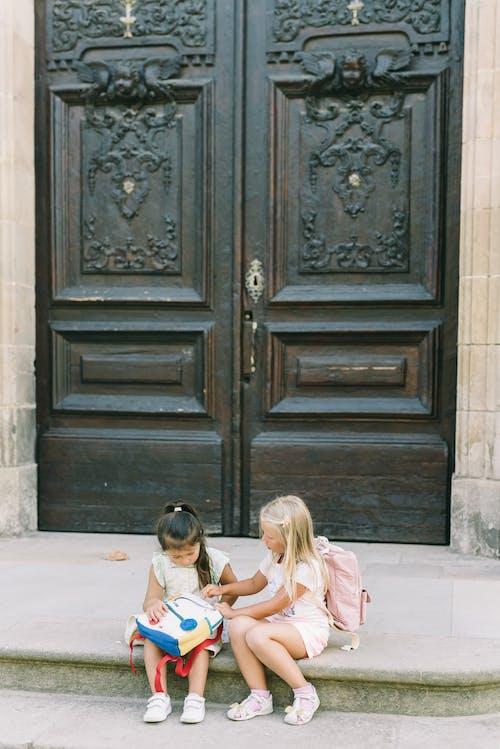 Kahverengi Ahşap Kapının Yanında Katta Oturan 2 Kız