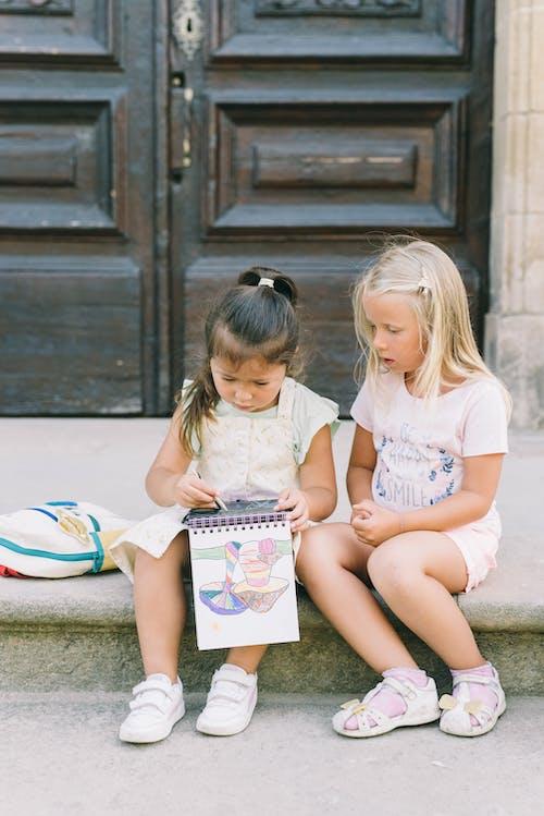 2 Meninas Sentadas No Chão De Concreto