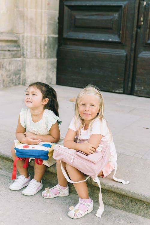 2 Meisjes Zittend Op Rode Plastic Stoel