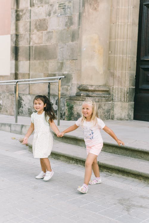 Gri Beton Zemin üzerinde Beyaz Elbiseli 2 Kız