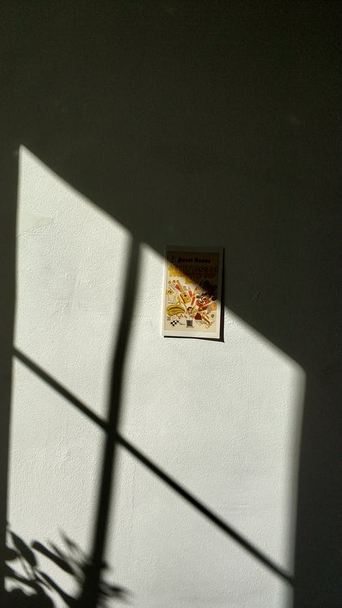 Shadow from window on wall with picture