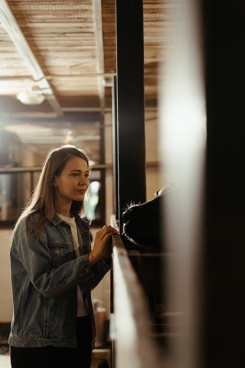 Woman in Blue Denim Jacket Standing Beside Glass Window
