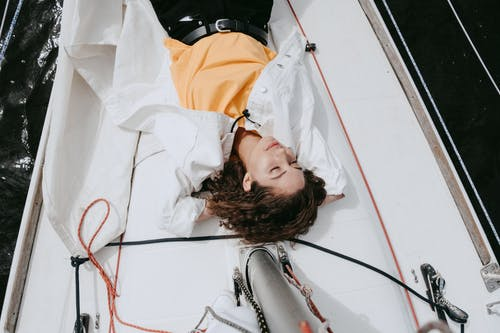 женщина в оранжево черной куртке, лежа на белой кровати