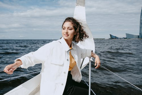 Woman in White Button Up Shirt and Black Pants Sitting on White Boat
