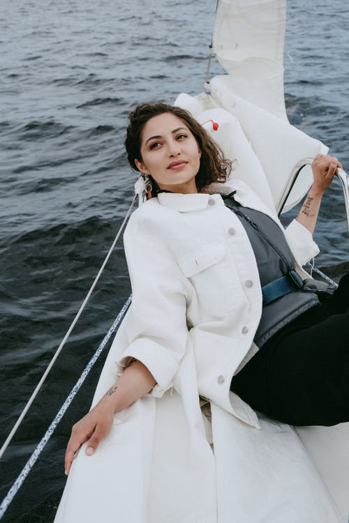 Woman in White Long Sleeve Shirt Sitting on Boat