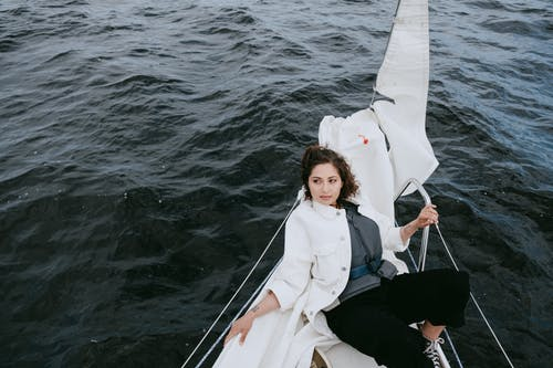 Woman in White Coat Sitting on White Boat
