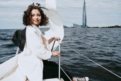 Женщина в белой рубашке с длинным рукавом и черном жилете стоит на лодке