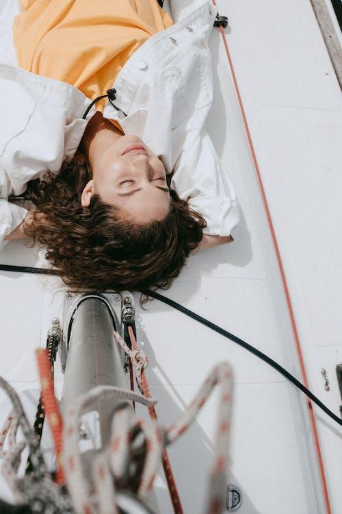 Женщина в белой рубашке, лежа на белой кровати