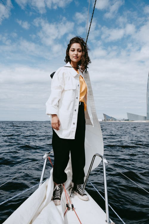 Woman in White Button Up Shirt and Black Pants Standing on Boat