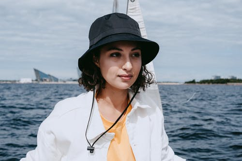 Woman in White Button Up Shirt Wearing Black Fedora Hat