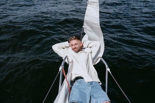 Женщина в белом худи и синих джинсовых шортах сидит на белой лодке