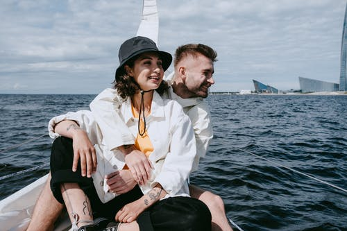 Man in White Dress Shirt Sitting Beside Woman in White Dress Shirt on Sea