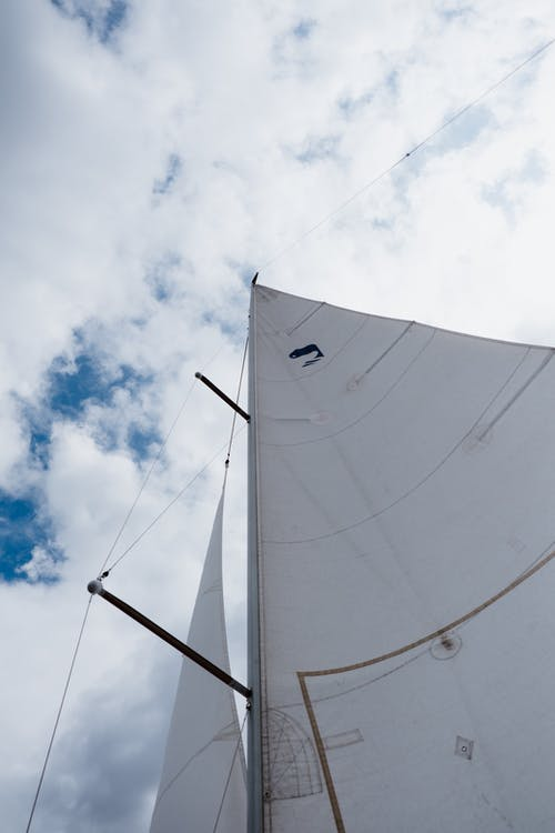 White Sail Boat on Water Under Blue Sky and White Clouds