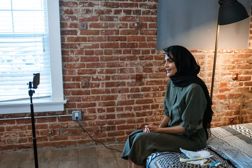 Woman in a Hijab Sitting on a Bed