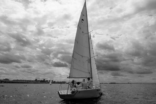 Grayscale Photo of Sail Boat on Sea Shore
