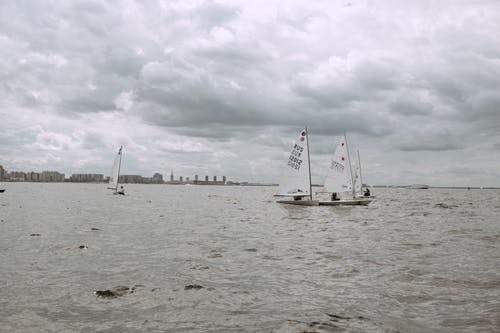 White Sail Boat on Sea Under White Clouds