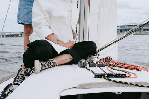 Pria Berkemeja Putih Duduk Di Atas Perahu Putih
