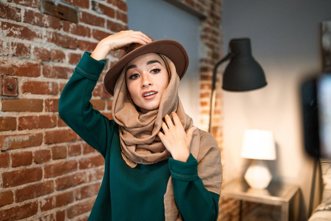Woman in Green Long Sleeved Shirt Wearing a Hat on Top of Her Brown Hijab
