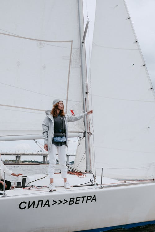 青いデニムジャケットと白いボートの上に立っている白いズボンの女性