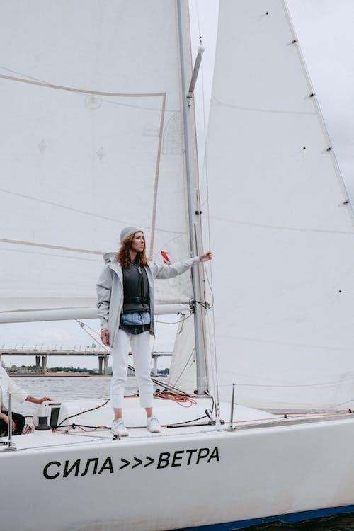 Женщина в синей джинсовой куртке и белых штанах стоит на белой лодке