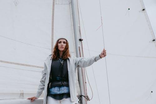 Wanita Dengan Jaket Hitam Dan Jeans Denim Biru Berdiri Di Atas Perahu Putih