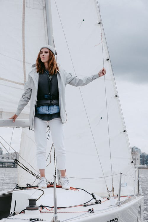 Woman in Gray Jacket and Blue Denim Jeans Standing on Dock