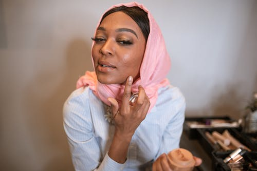 Woman in White Long Sleeve Shirt and Pink Hijab Applying Make-up