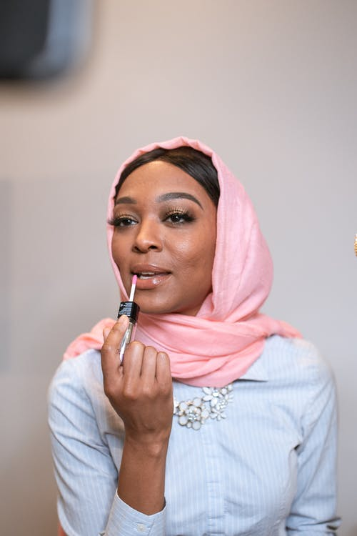 Woman in Pink Hijab Applying Lipstick