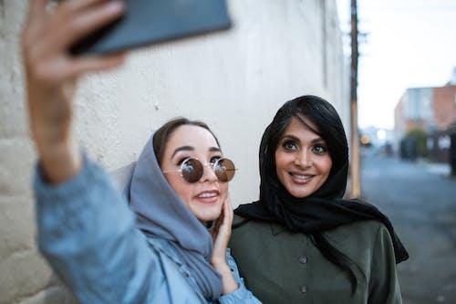 Woman in Blue Jacket Wearing Sunglasses Beside Woman in Black Hijab