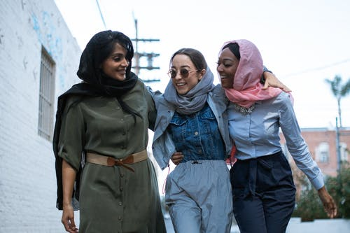 2 Women in Pink Hijab Standing Near Man in Gray Jacket