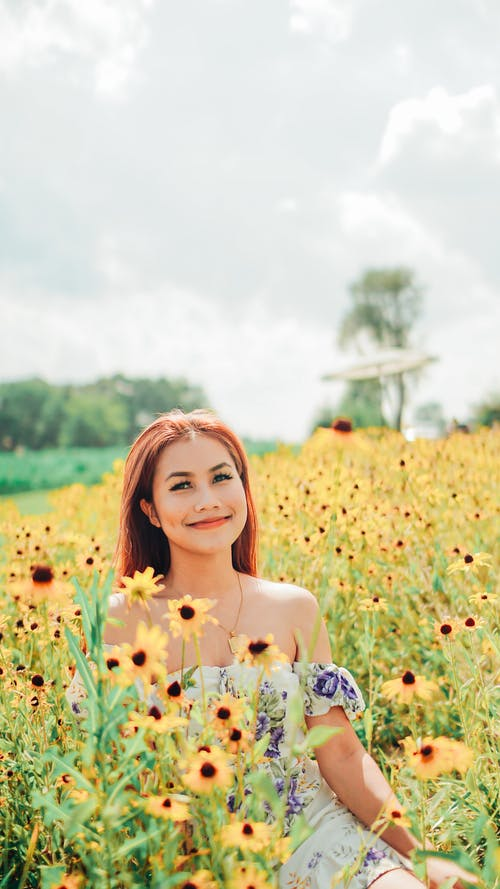 Woman in White and Blue Floral Dress on Yellow Flower Field