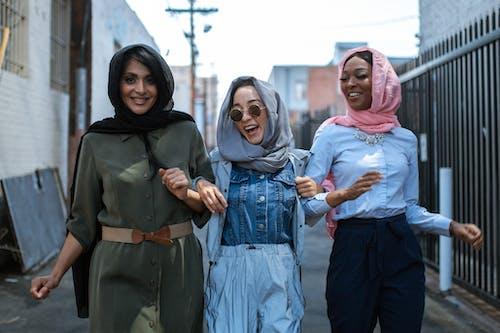 Joyful multiethnic women in headscarves walking on street