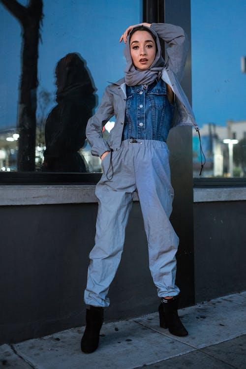 Woman in Blue Denim Jacket and Blue Denim Jeans Standing Beside Black Concrete Wall