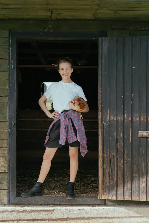 Woman in White Crew Neck T-shirt and Purple Skirt Standing Beside Brown Wooden Wall