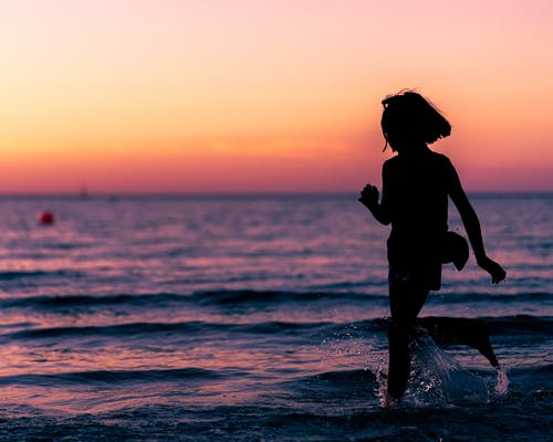 Side view of anonymous barefooted little girl having fun in sea at sunset during rest
