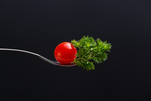 Ripe red tomato and sprig of greenery