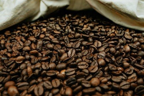 Abundance of bright roasted coffee beans near fabric