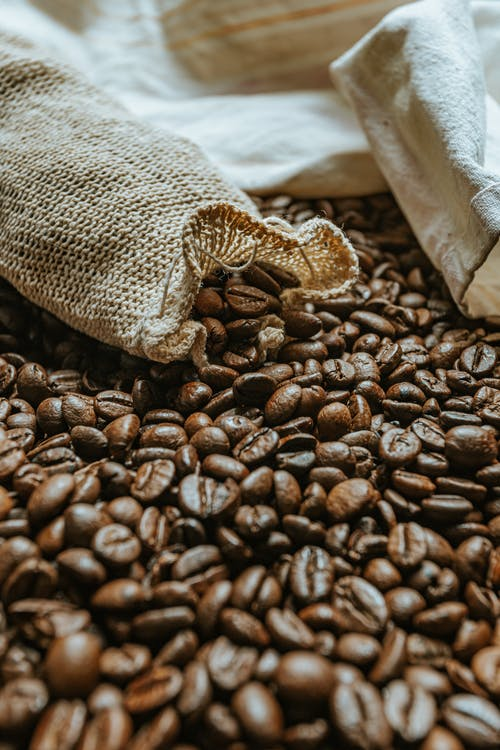 Zero waste bags on heap of roasted coffee beans