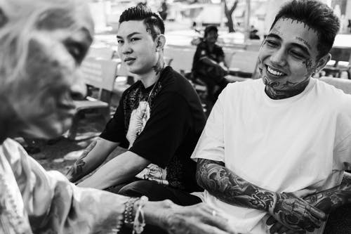 Cheerful tattooed Asian men communicating with elderly woman