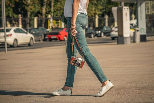 Woman in White Shirt and Blue Denim Jeans Walking on Street