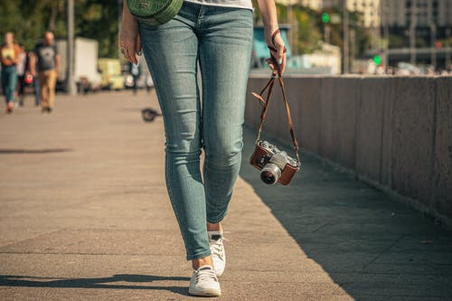 Woman in Blue Denim Jeans and White Sneakers Holding Red and Black Backpack Walking on Street